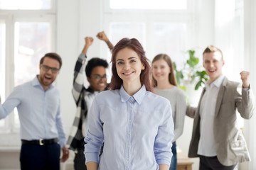 Portrait of smiling female employee standing foreground, excited team or colleagues cheering at background, successful woman professional look at camera posing in office. Leadership concept