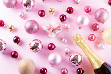 Christmas party with neck of champagne bottle and gift box on pink background