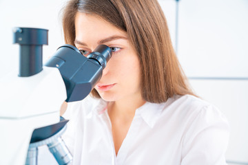 Young woman technician is examining a histological sample, a biopsy in the laboratory of cancer research
