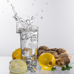 A glass of lemonade on a light background with splashing water