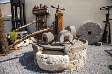 Old mill for grinding olives. An antique machine for producing olive oil.
