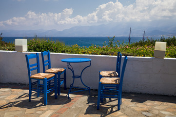Blue chairs and tables in the restaurant. A place to eat on the seashore.