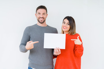 Fototapeta Young couple holding blank sheet paper over isolated background very happy pointing with hand and finger obraz