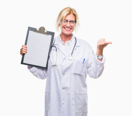 Middle age blonde doctor woman holding clipboard over isolated background pointing and showing with thumb up to the side with happy face smiling