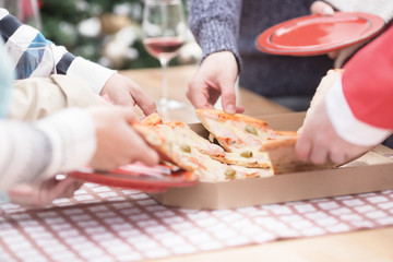 Young friends eating Pizza on Christmas