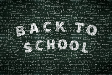 A lot of basic math equations and formulas with back to school phrase, white chalk lettering on black chalkboard
