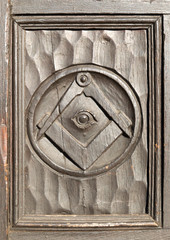 Historic carved masonic symbols on wooden panel on door of house in Marlborough, Wiltshire, England, UK