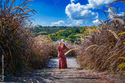 Wall mural Young woman walking on wooden path.