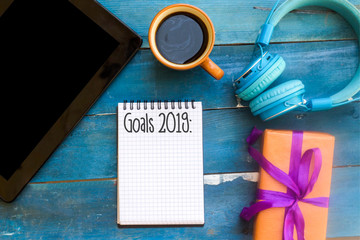 goals 2019 in notebook on blue wooden table