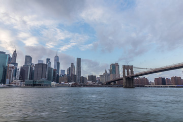 Fototapete - View of Manhattan with Brooklyn Bridge at sunset from the side of the pier.