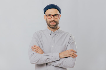 Horizontal shot of satisfied self confident male designer wears stylish headgear, dressed in white shirt, keeps arms folded, has dark stubble, isolated over white background. People and style concept
