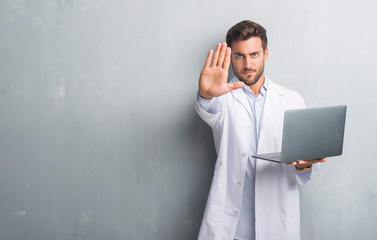 Handsome young man over grey grunge wall wearing white coat using laptop with open hand doing stop sign with serious and confident expression, defense gesture
