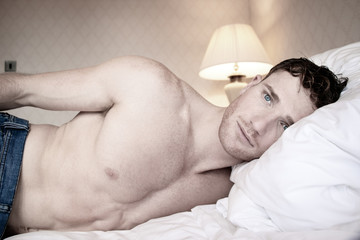 Handsome hunky shirtless man with blue eyes and jeans lying on hotel room bed sheets