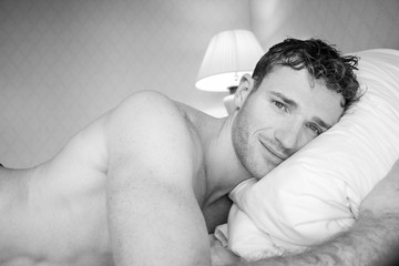 Black and white picture of handsome naked man lying on hotel room bed sheets