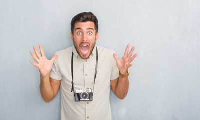 Handsome young man over grey grunge wall holding vintage photo camera very happy and excited, winner expression celebrating victory screaming with big smile and raised hands