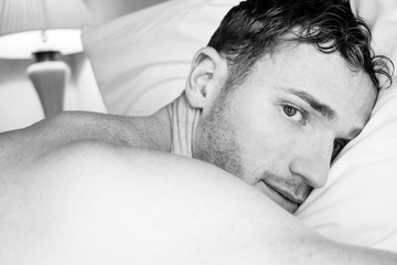 Sexy handsome shirtless man with beard lying on hotel bed pillow and looking at camera