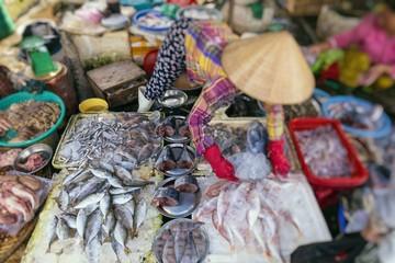 Street Vendor in Hue, Vietnam traditional fish market people selling fresh fish on the sidewalk.