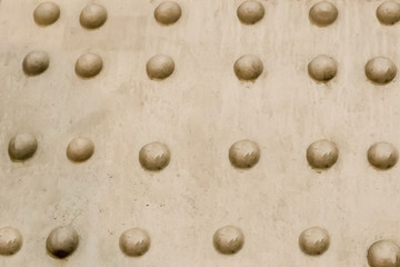 abstract background industrial metal base beige surface rivets row uneven surface