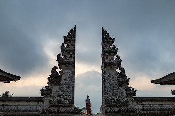 Man is standing in the gate of Pura Lempuyang temple. Mount Agung on the background. Bali island, Indonesia