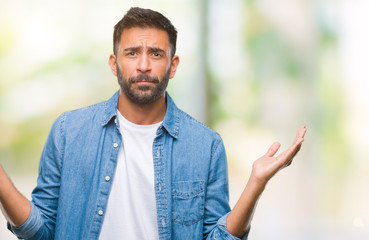 Adult hispanic man over isolated background clueless and confused expression with arms and hands raised. Doubt concept.