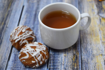 A Cup of fragrant tea and delicious sweet cookies on a wooden background.