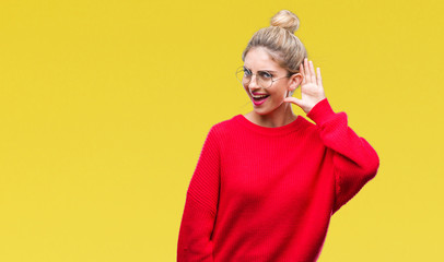Young beautiful blonde woman wearing red sweater and glasses over isolated background smiling with hand over ear listening an hearing to rumor or gossip. Deafness concept.