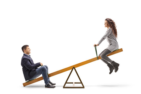 Young man and woman playing on a seesaw