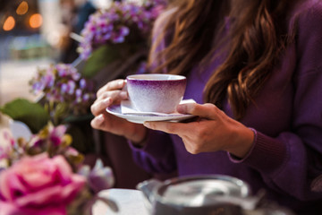 Close-up of a woman who is sitting in the restaurant outdoor and holding a cup of tea