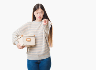 Young Chinese woman over isolated background holding a box pointing with finger to the camera and to you, hand sign, positive and confident gesture from the front