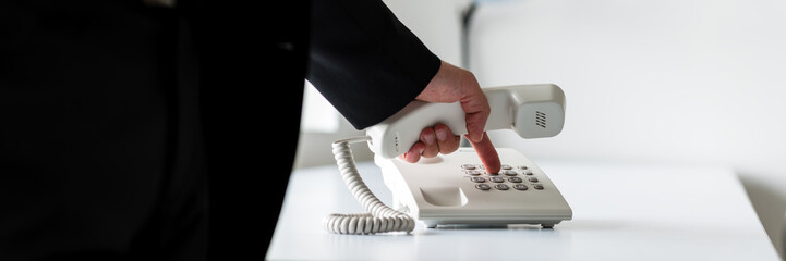 Wide view image of businessman dialing telephone number