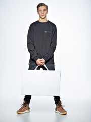 Teen boy with shopping bags at studio.