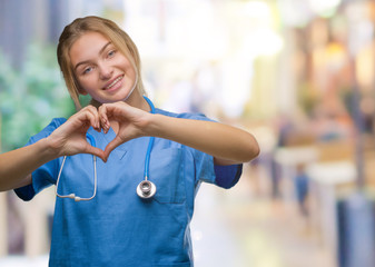 Young caucasian doctor woman wearing surgeon uniform over isolated background smiling in love showing heart symbol and shape with hands. Romantic concept.