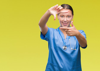 Young caucasian doctor woman wearing medical uniform over isolated background smiling making frame with hands and fingers with happy face. Creativity and photography concept.