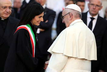 Pope Francis shakes hands to Rome's mayor Virginia Raggi as he arrives to leads the Immaculate Conception celebration prayer in Piazza di Spagna in downtown Rome