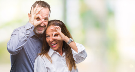 Middle age hispanic business couple over isolated background doing ok gesture with hand smiling, eye looking through fingers with happy face.
