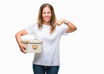 Middle age hispanic woman moving holding packing box over isolated background with surprise face pointing finger to himself