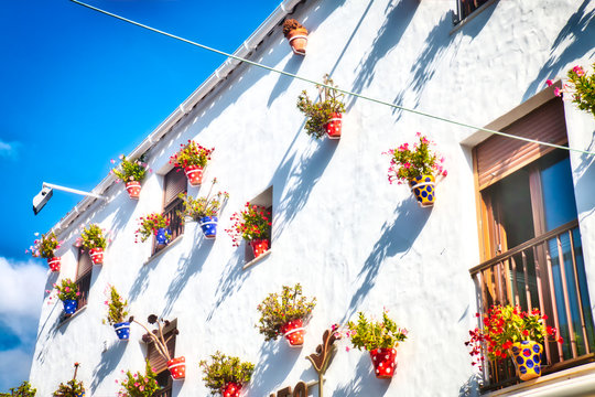 Typical Andalusian house facade, full of pots with flowers, in Conil de la Frontera, a beautiful and touristic village in the province of Cadiz, Southern Spain