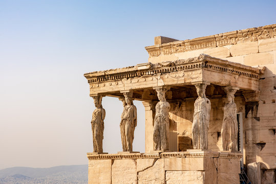 The ancient Erechtheion temple with the beautiful Caryatid pillars on the porch, with a golden glow at sunset, on the Acropolis in Athens, Greece.