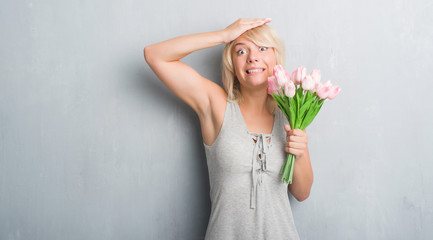 Caucasian adult woman over grey grunge wall holding pink flowers stressed with hand on head, shocked with shame and surprise face, angry and frustrated. Fear and upset for mistake.