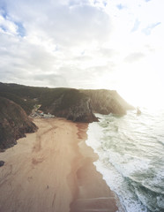 Aerial view from a sandy beach at the sunset with an amazing cliff. Adraga beach Sintra, Portugal
