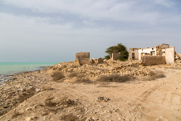 Ruined ancient old Arab pearling and fishing town Al Jumail, Qatar. The desert at coast of Persian Gulf. Deserted village on the beach of sea