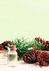 Essential pine tree oil, fir tree branches with cones, vertical green aromatherapy set. Winter home scents & spa