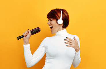 Listening to music. Woman portrait. Emotions. Girl with short red hair and in headphones is singing with a hairbrush, on an orange background