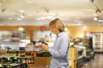 Teenager shopping in supermarket, reading product information