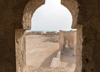 Ruined ancient Arab pearling, fishing town Al Jumail, Qatar. Desert at coast of Persian Gulf. Lost village. A view out of minaret's window to the sea