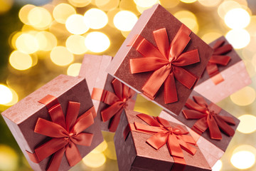 Many traditional gift boxes fall or fly on a festive golden background. Holiday concept