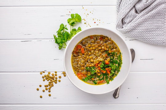 Homemade vegan lentil soup with vegetables and cilantro, white wooden background.