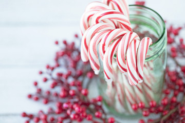 Christmas photograph of candy canes in a green mason jar with red berries on white