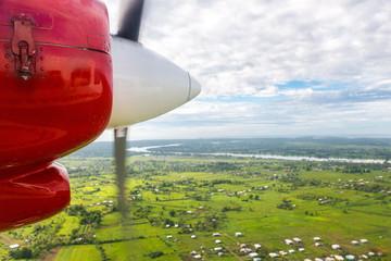 Air travel in Fiji, Melanesia, Oceania. View of Rewa river, Nausori town, Viti Levu island from a window of a small turboprop propeller airplane.