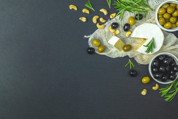 Set of cheese camembert, black and green olives, quail eggs, olive oil and rosemary